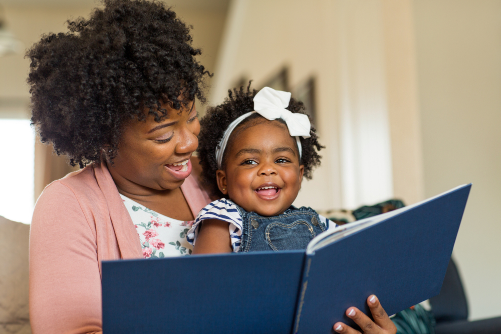 Photo: Mother reading to a smiling toddler who is sitting on her lap.