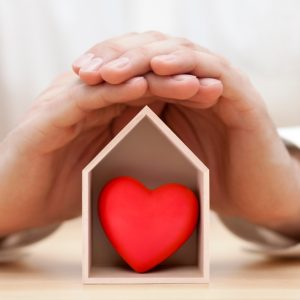 Photo: Hands cradle a house-shaped box with red heart inside