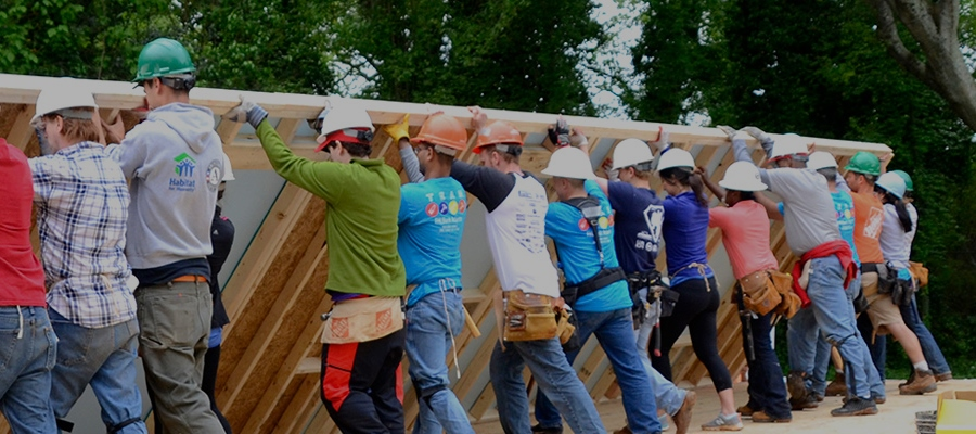 Image description: Staff at TechBridge - an official Exponent Case Management implementation partner - working together to build a home and lift a wall. Source: Techbridge.org
