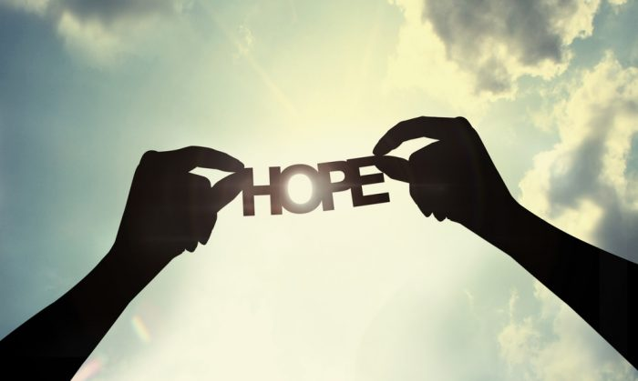 Hope Photo: Two hands hold letters towards the sky that spell the word hope as sun rays beam down.