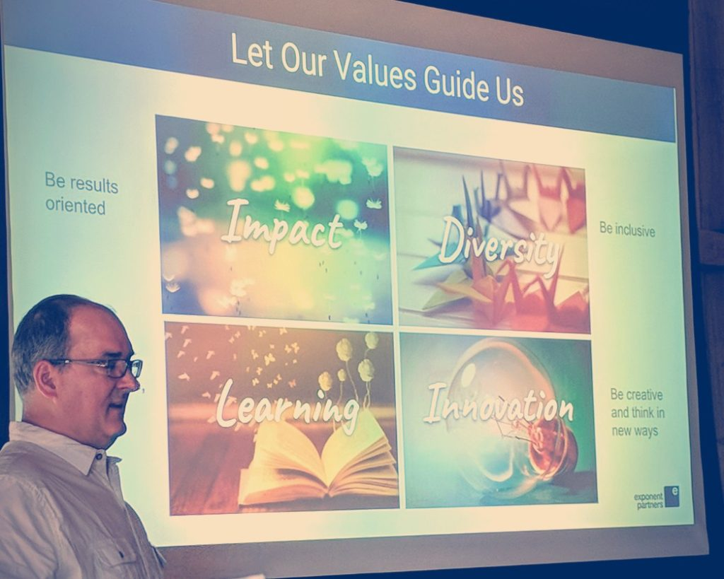 Photo: Founder Rem Hoffmann stands in front of a projection screen that lists our values: diversity, learning, innovation, and impact.