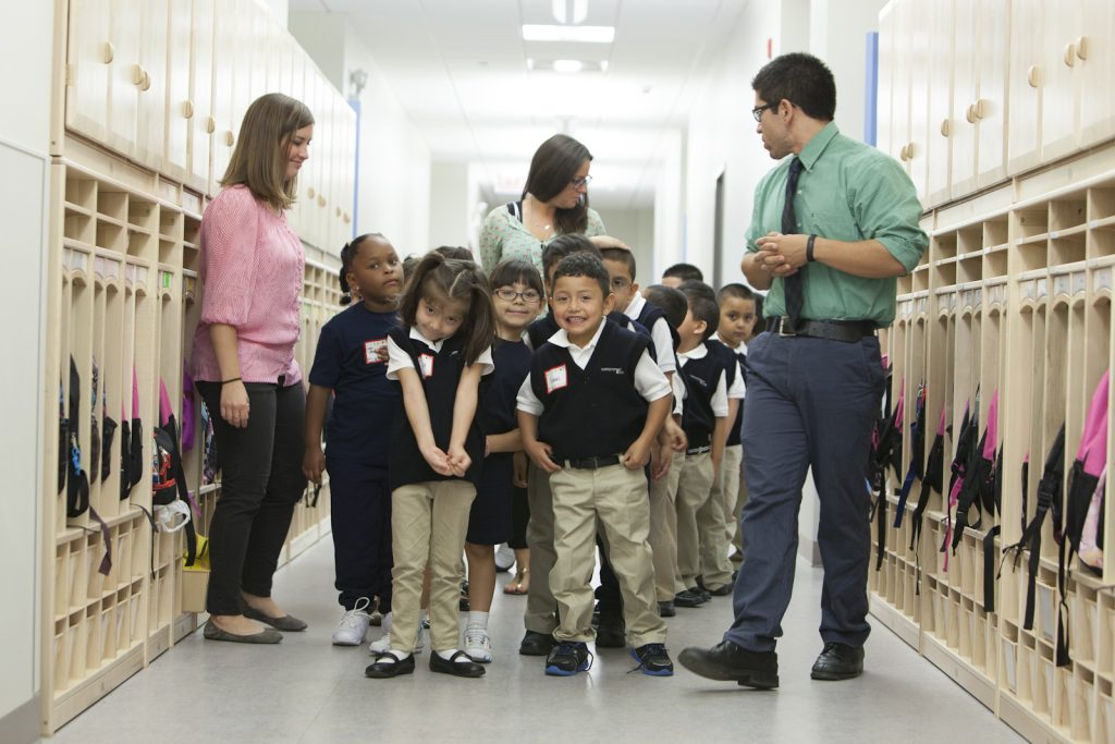 Photo: children at Christopher House walk down hallway with instructors.