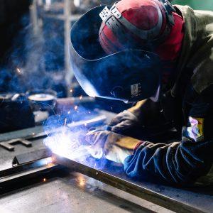 Photo: Member of workforce welding metal in factory workshop.