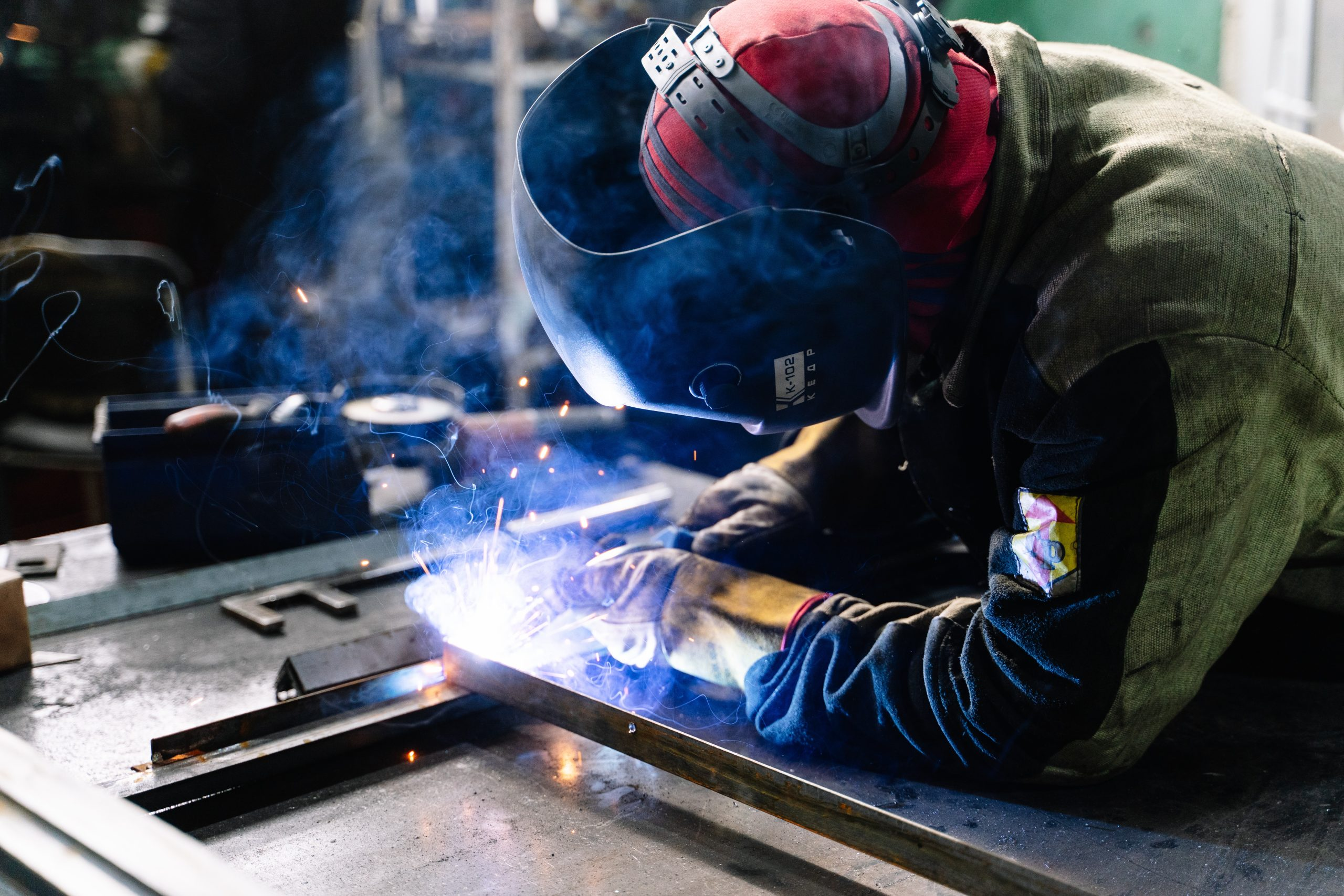 Photo: Member of workforce welding metal in factory workshop.