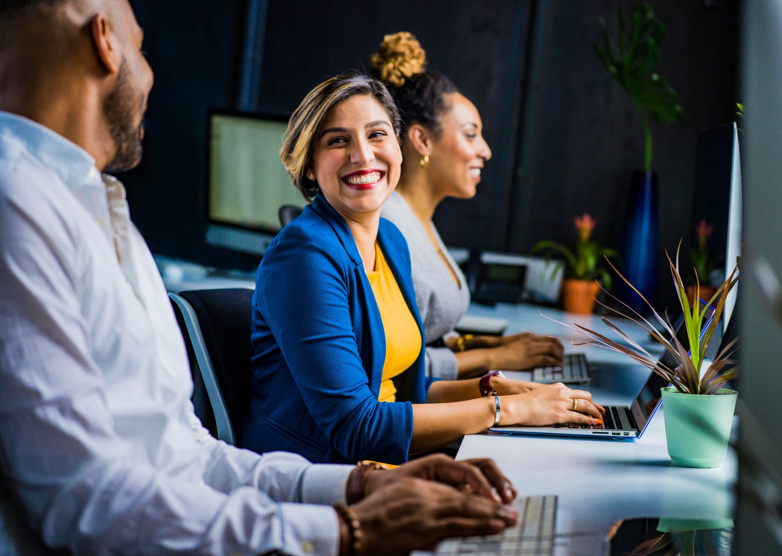 Photo: Woman in workforce smiling at office coworkers.