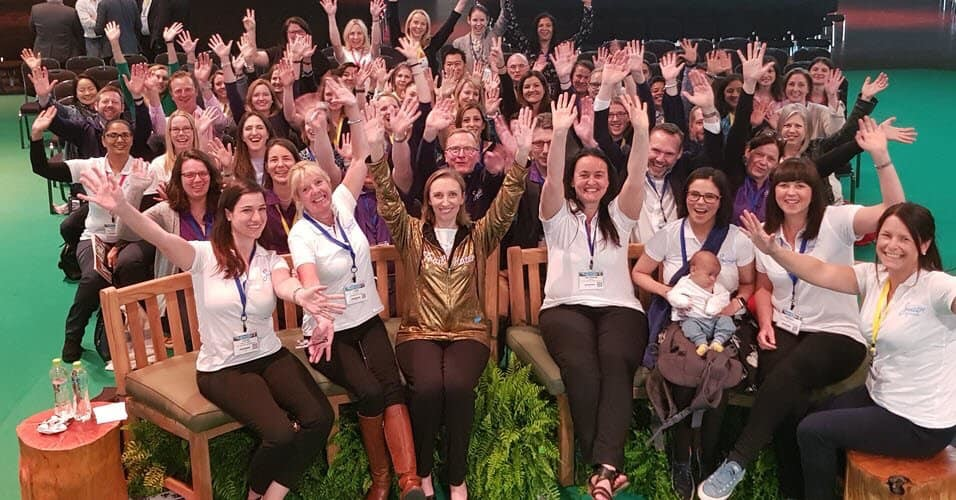 Photo: large group of SuperMums trainees waving at the camera.