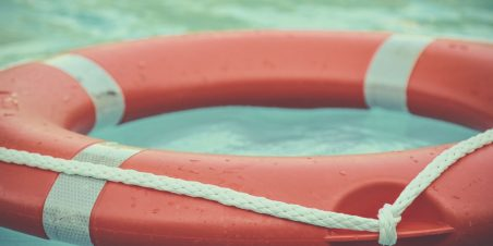Photo: Orange and white life buoy floating at sea.