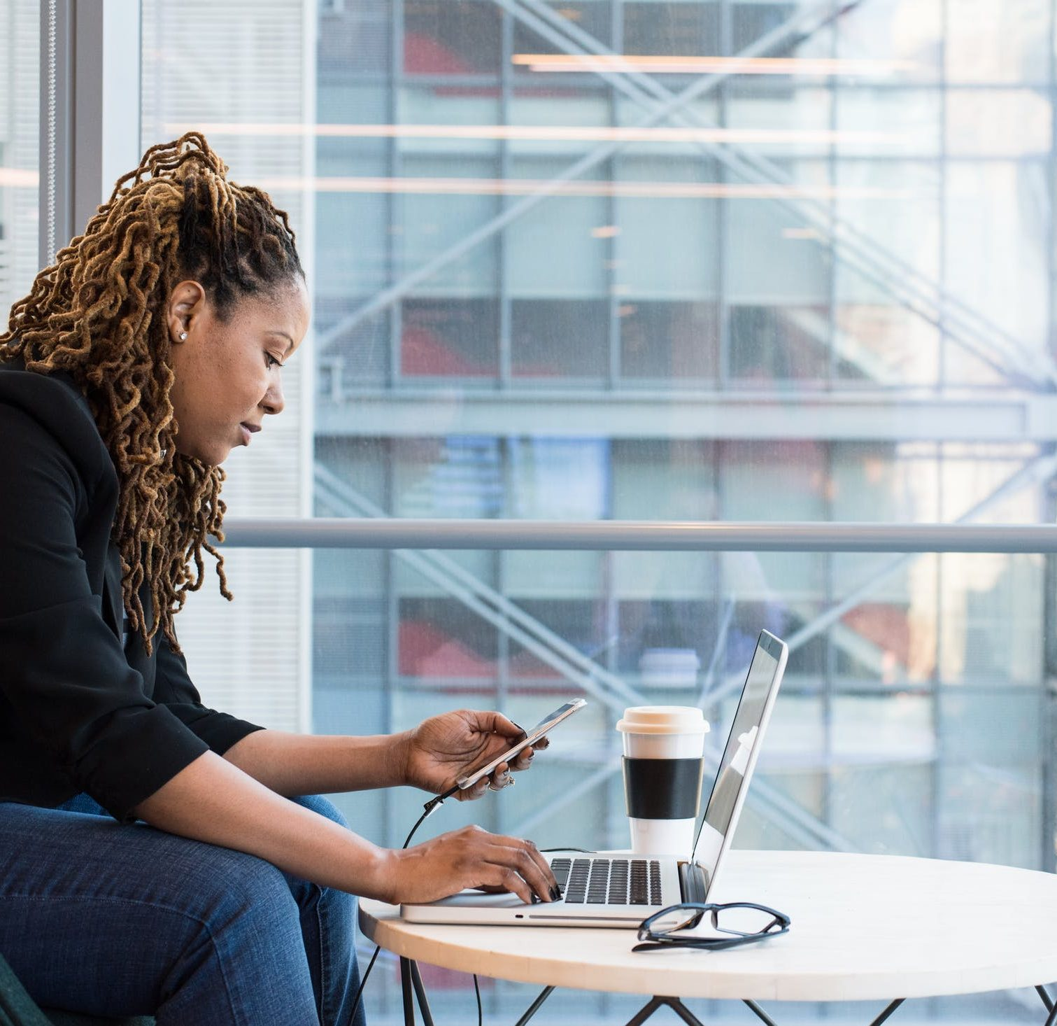 Photo: Woman with smartphone and coffee conducting remote work.