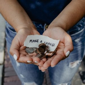 "Photo: hands offering money with a note that reads ""Make a Change"""