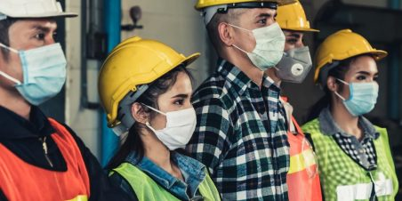 Photo: Men and women warehouse workers standing next to each other while wearing protective masks.