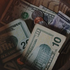 Photo: Cash and coins placed in a wooden donation bowl.