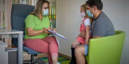 Photo: Case worker wearing a pandemic mask meeting with father and child also wearing pandemic masks for a services assessment