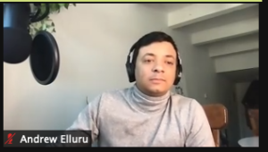 Photo: Andrew wearing a turtleneck sitting at a professional audio microphone.