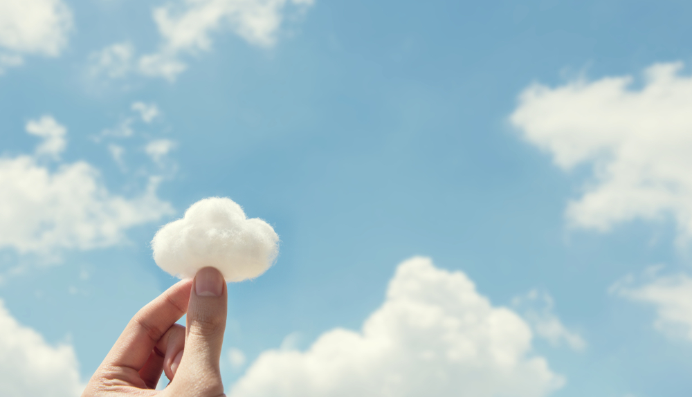 Photo: Two fingers pinched together to hold a tuft of cotton shaped like a cloud with blue sky and real clouds in the background.