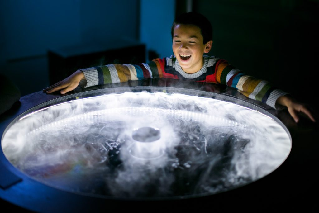 Photo: Young boy smiling enjoying a science exhibit at The Exploratorium.