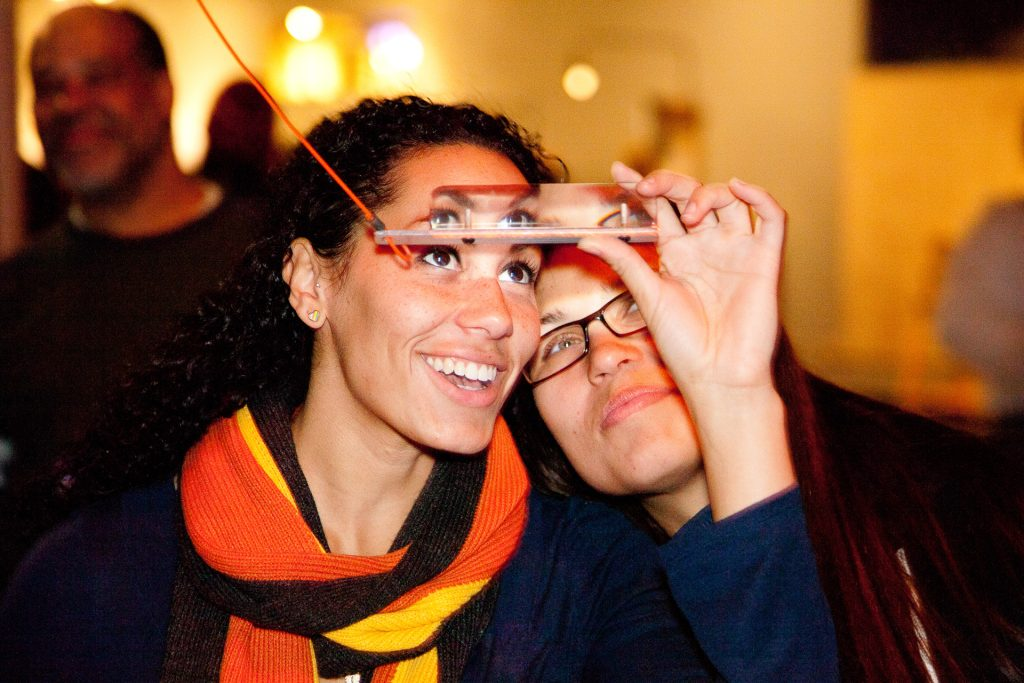 Photo: Two women smiling looking through the prism glass at the Exploratorium.