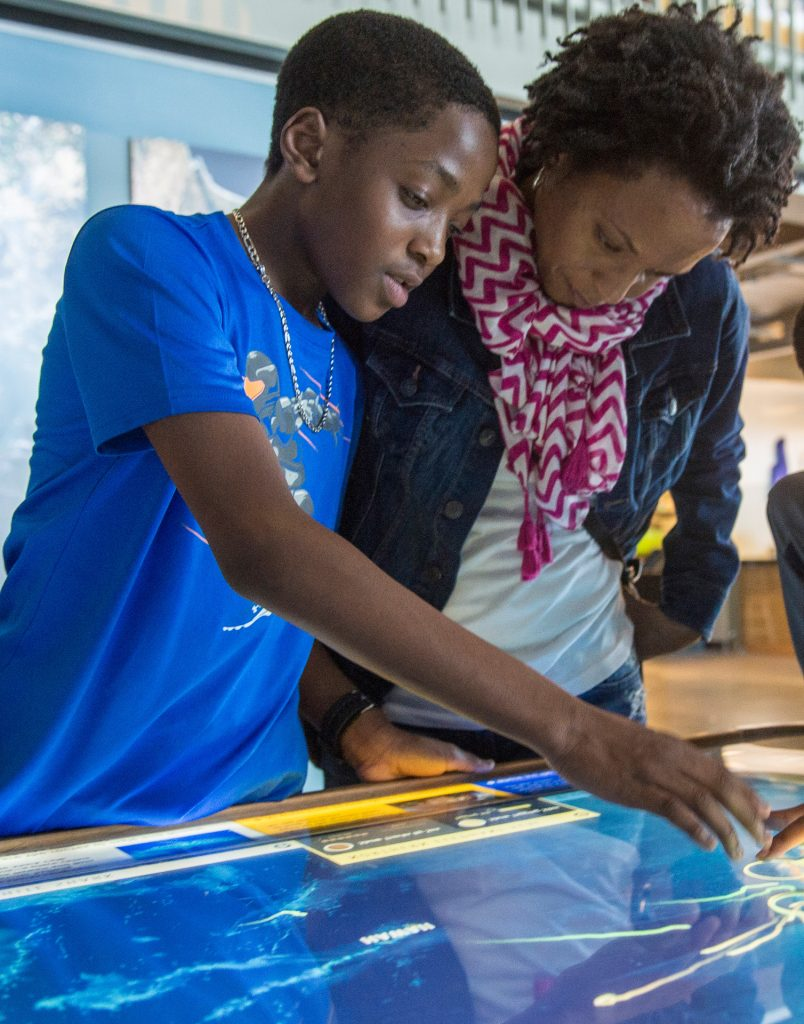 Photo: A woman and boy interact with an exhibit at the Exploratorium.